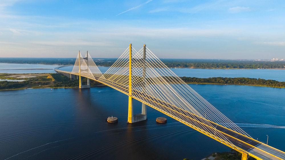 Pont suspendu jaune passant au dessus d'une étendue d'eau